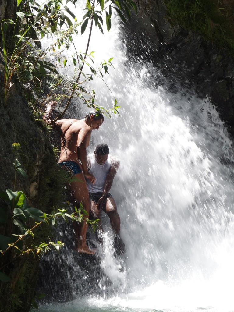 Two adventurers climb into the waterfalls.